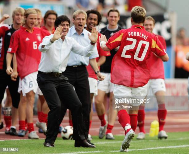 Juergen Klinsmann the German coach and his assistant Joachim Loew celebrate with goalscorer Lukas Podolski during the FIFA Confederations Cup 2005...