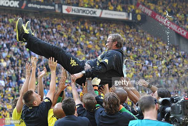 Juergen Klopp head coach of Dortmund is tossed in the air by his players after winning the league title at the end of the Bundesliga match between...
