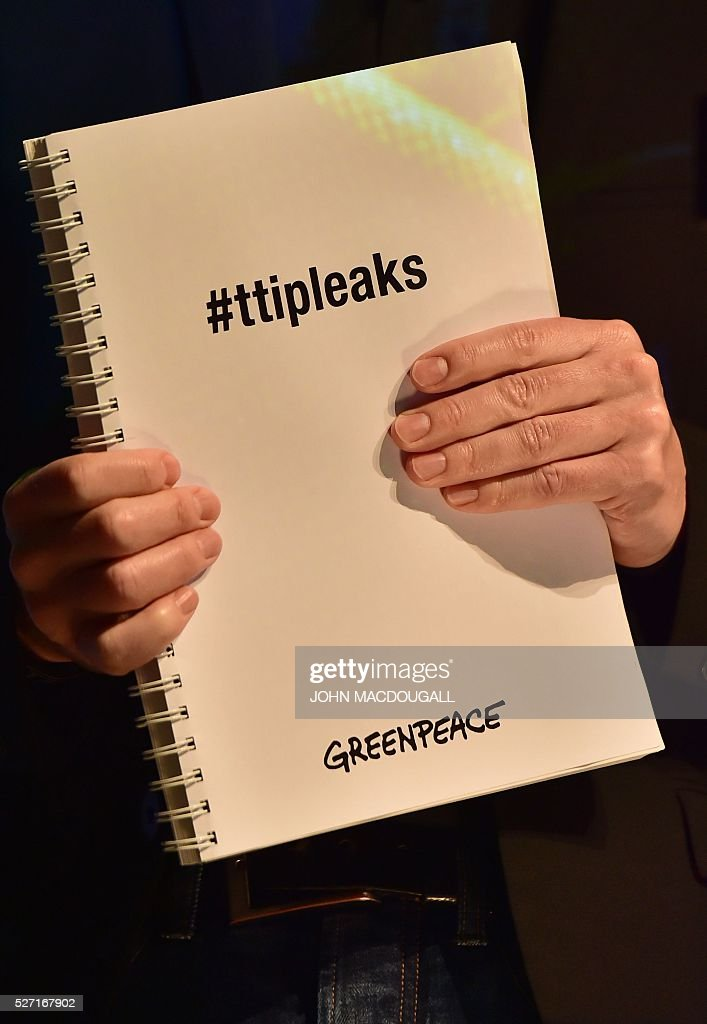 Juergen Knirsch, Greenpeace trade expert, holds a document with classified papers from ongoing US-EU trade talks with the 'ttipleaks' hashtag on its title during a press conference on May 2, 2016 at the re:publica conference on internet and society in Berlin. Greenpeace published documents showing that the Transatlantic Trade and Investment Partnership (TTIP) poses 'major risks for climate, environment and consumer safety'. / AFP / John MACDOUGALL