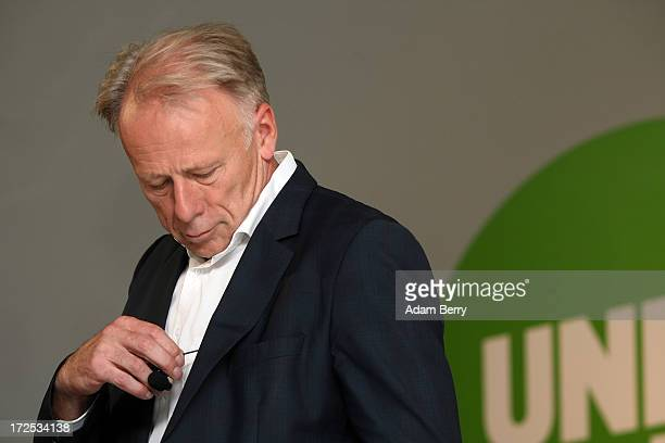 Juergen Trittin coleading candidate of the German Green Party for the country's 2013 federal election removes a lapel microphone during the launch of...