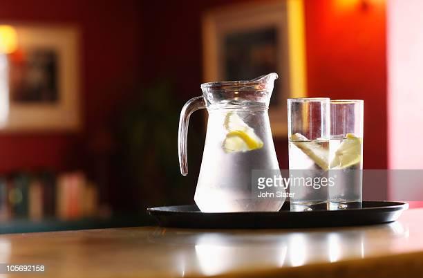 jug and glasses of water at bar