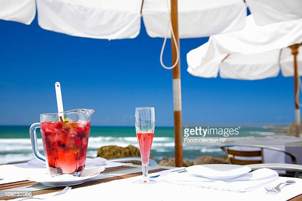 Jug of sangria with berries and sparkling wine on table by sea