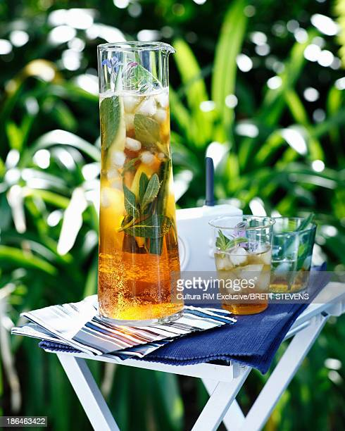 Jug of pimms and lemonade with ice cubes and garnish
