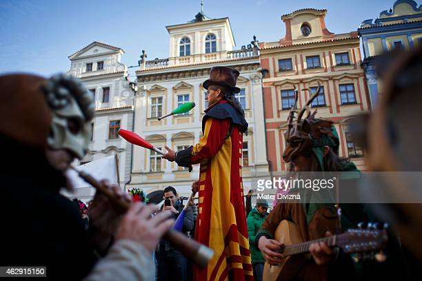 A juggler shows his skills as musicians dressed in costumes play musicial instruments as they celebrate the opening of the Carnevale Praga 2015...