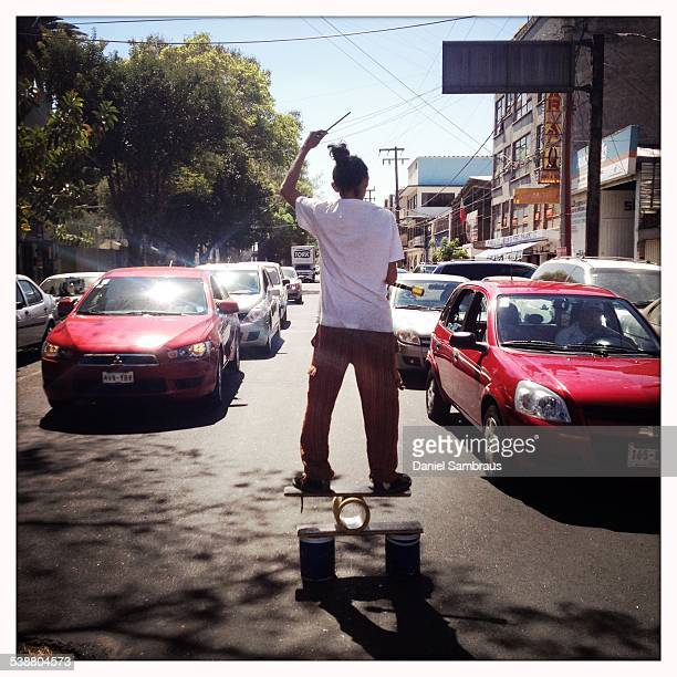A juggler street artist entertaining drivers at a red light Mexico City Mexico