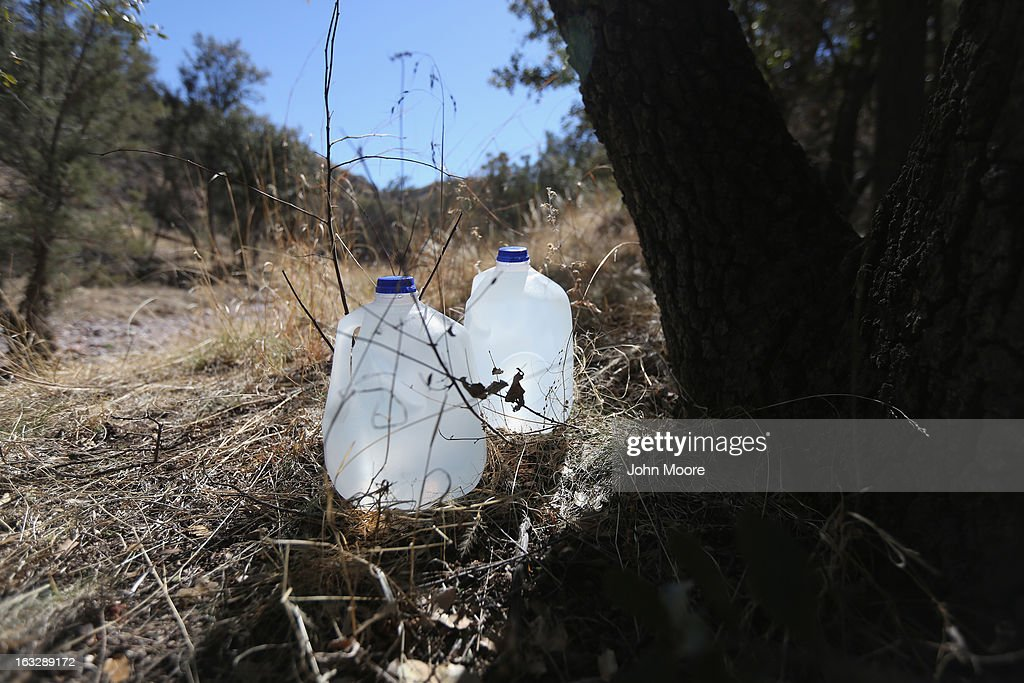 Jugs of drinking water sit along an immigrant trail near the Mexican border fence on March 6, 2013 in Walker Canyon, Arizona. Volunteers for the non-profit The Samaritans group distributes water along the trails with the aim of reducing immigrant deaths due to dehydration during their long trek from Mexico into the United States, often through remote desert areas.