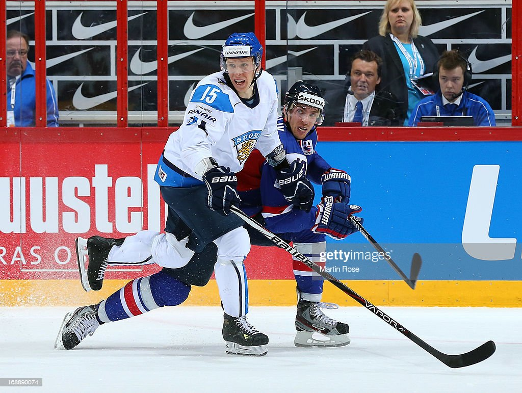 Juha Hytonen (L) of Finland and Michel Miklik (R) of Slovakia battle for the puck during the IIHF World Championship quarterfinal match between Finland and Slovakia at Hartwall Areena on May 16, 2013 in Helsinki, Finland.