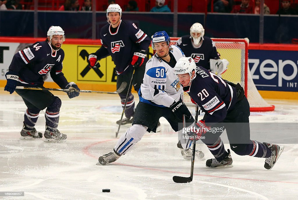 Juhamatti Aaltonen (L) of Finland and Ryan Carter (R) of USA battle for the puck during the IIHF World Championship third place match between Finland and USA at Globen Arena on May 19, 2013 in Stockholm, Sweden.