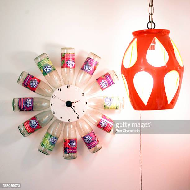 Juice bottle clock on wall in den of Joan Currie's 640 square foot apartment which is alive with clever ideas about how to decorate using what you...