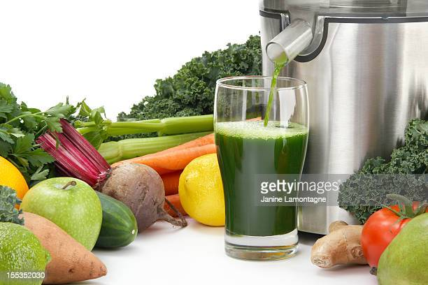 Juicer pouring juice into glass surrounded by vegetables