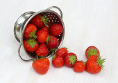 Juicy, ripe strawberries spill from colander