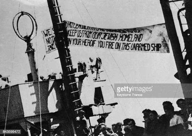 Juifs arrivent sous escorte à bord d'un bateau dans le port d'Haifa où ils sont accueillis par des coups de feu malgré une banderole indiquant en...