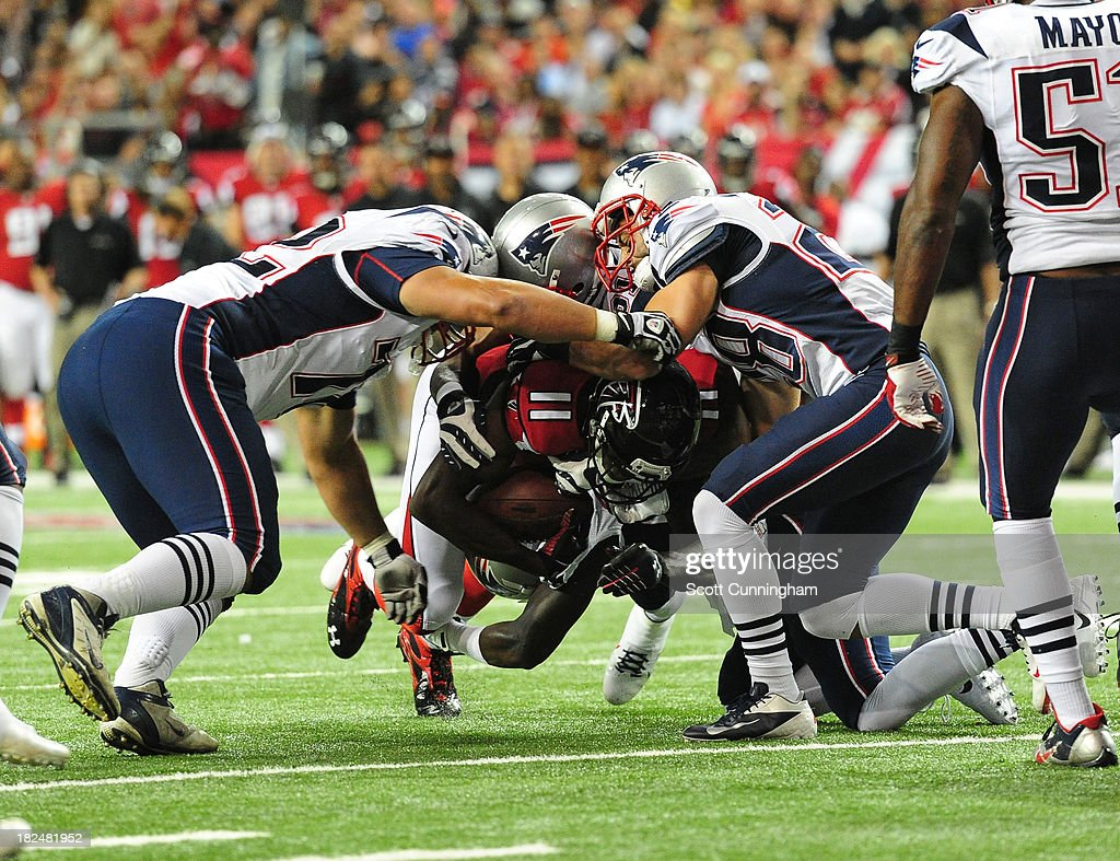 Juio Jones #11 of the Atlanta Falcons is tackled by <a gi-track='captionPersonalityLinkClicked' href=/galleries/search?phrase=Joe+Vellano&family=editorial&specificpeople=7256652 ng-click='$event.stopPropagation()'>Joe Vellano</a> #72 and Steve Gregory #28 of the New England Patriots at the Georgia Dome on September 29, 2013 in Atlanta, Georgia.
