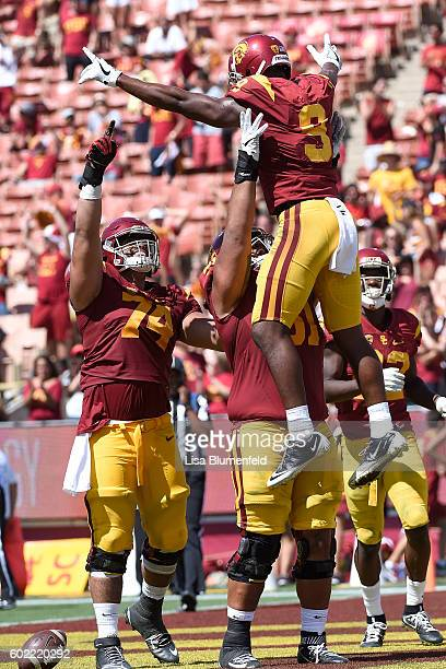 JuJu SmithSchuster of the USC Trojans celebrates with teammates Nico Falah and Damien Mama after scoring a touchdown in the 4th quarter against the...