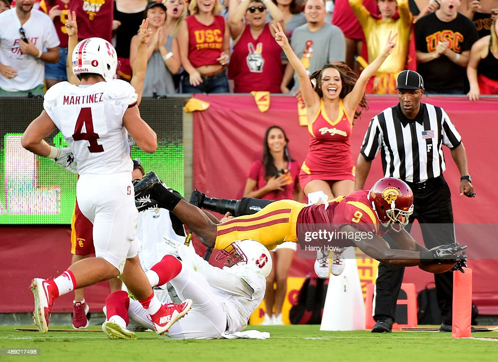 JuJu Smith-Schuster #9 of the USC Trojans dives over Kodi Whitfield #5 of the Stanford Cardinal for a touchdown as Blake Martinez #4 follows the play to take a 21-10 lead during the second quarter at Los Angeles Coliseum on September 19, 2015 in Los Angeles, California.