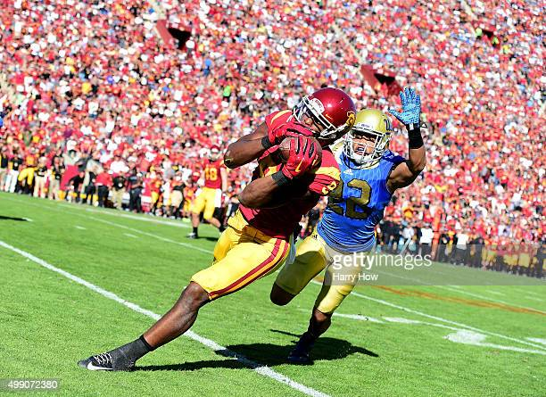 JuJu SmithSchuster of the USC Trojans makes an over the shoulder catch in front of Nate Meadors of the UCLA Bruins for a first down during the second...
