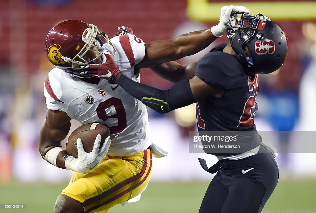 JuJu Smith-Schuster #9 of the USC Trojans stiff arms Ronnie Harris #21 of the Stanford Cardinal during the second quarter of the NCAA Pac-12 Championship game at Levi's Stadium on December 5, 2015 in Santa Clara, California.