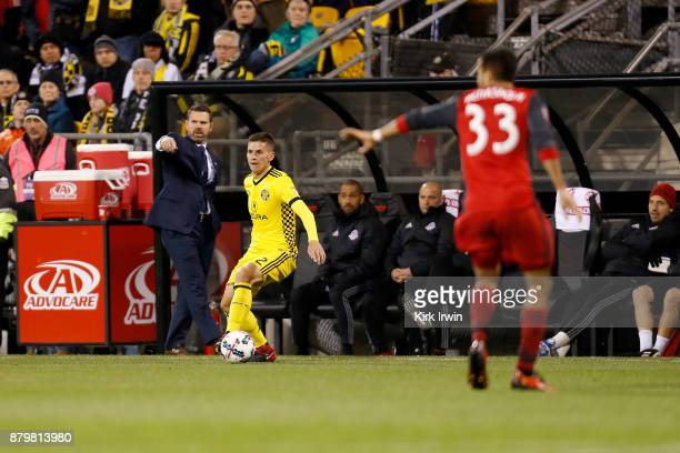 Jukka Raitala of the Columbus Crew SC controls the ball as head coach Greg Vanney of the Toronto FC calls out to his players during the match at...
