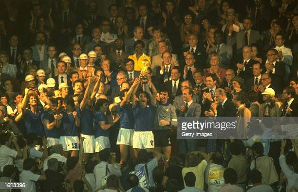 Spectators surround the Italian World Champions as they hold aloft the trophy after winning the World Cup Final against West Germany at the Santiago...