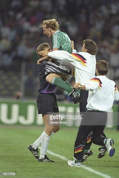 Andreas Brehme of West Germany is lifted by goalkeeper Bodo Illgner after their victory in the World Cup semifinal against England at the Delle Alpi...