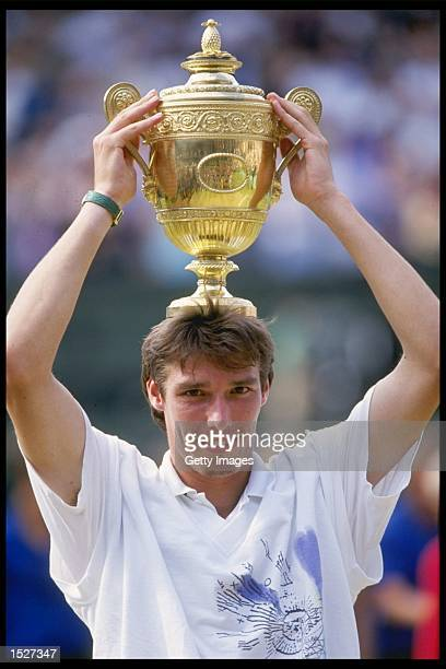Michael Stich of Germany holds aloft the mens singles trophy after defeating Boris Becker of Germany in straight sets during the Wimbledon tennis...