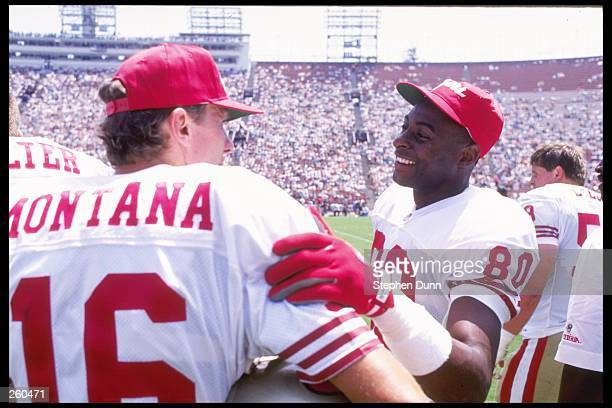 Quarterback Joe Montana and wide receiver Jerry Rice of the San Francisco 49ers talk to each other during a preseason game against the Los Angeles...
