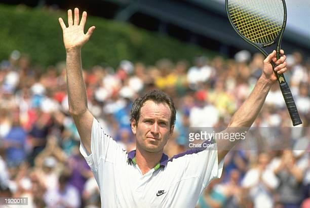 John McEnroe of the USA holds his arms aloft in victory after beating Andre Olhovskiy of Russia during the Lawn Tennis Championships at Wimbledon in...