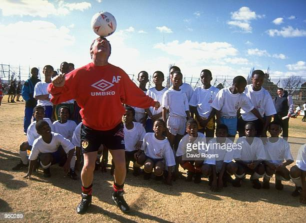 Manchester United manager Alex Ferguson coaches local children in Soweto during their tour to South Africa Mandatory Credit Dave Rogers /Allsport