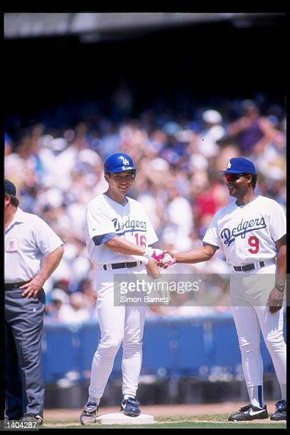 Pitcher Hideo Nomo of the Los Angeles Dodgers gets congratulations from teammate Reggie Smith after getting a base hit during a game against the...