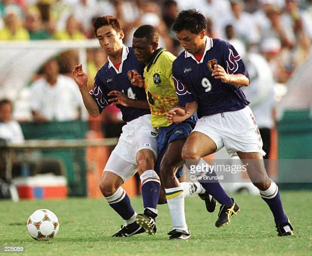 Amaral of Brazil is challenged by Hidetoshi Nakata and Shoji Jo of Japan during their match at the Orange Bowl Stadium in Miami in the 1996...