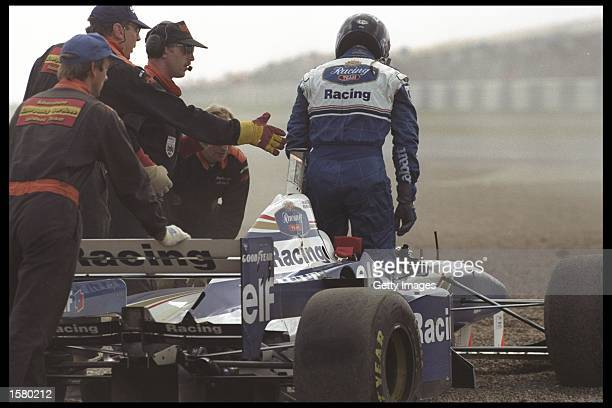 Damon Hill of Great Britain is helped out of his car after engine trouble caused him to spin off during the British grand prix at Silverstone England...