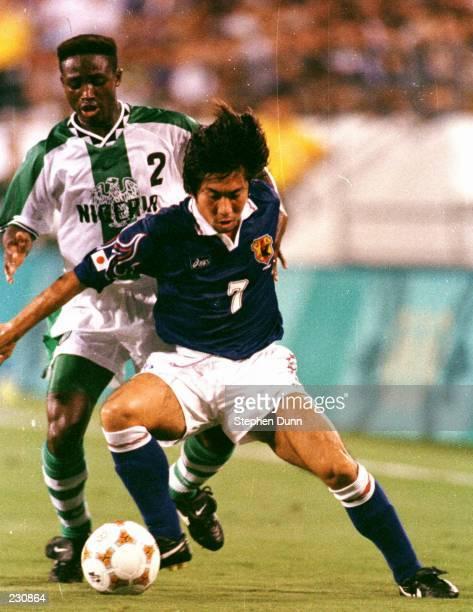 Masakiyo Maezono of Japan battles C Celestine Babayaro of Nigeria for the ball during Nigeria''s 20 victory at the Florida Citrus Bowl in Orlando...
