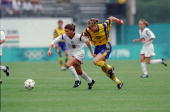 Mia Hamm of Team USA runs for the ball with Cecilia Sandell of Team Sweden during the 1996 Olympic Games at the Citrus Bowl in Orlando Florida Team...