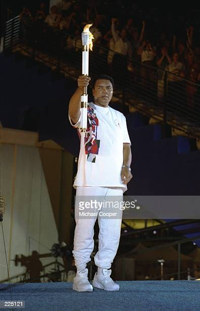 Muhammad Ali holds the torch before lighting the Olympic Flame during the Opening Ceremony of the 1996 Centennial Olympic Games in Atlanta Georgia