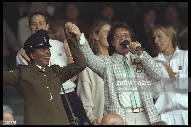 Sir Cliff Richard orchestrates the singing as the crowd join in on another rain delayed days play during the Wimbledon tennis championships at the...