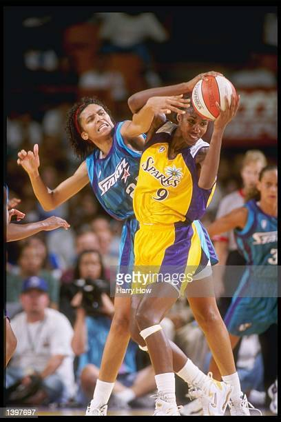Jessie Hicks of the Utah Starzz grabs for the ball held by Lisa Leslie of the Los Angeles Sparks during a game at the Great Western Forum in...