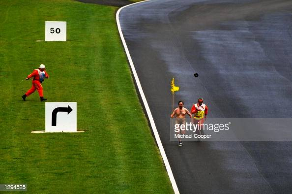 A streaker runs on the track before the British Grand Prix at the Silverstone circuit in Northampton England Mandatory Credit Michael Cooper/Allsport
