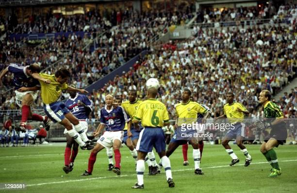 Zinedine Zidane of France rises above Leonardo of Brazil to score the opening goal in the World Cup Final at the Stade de France in St Denis France...