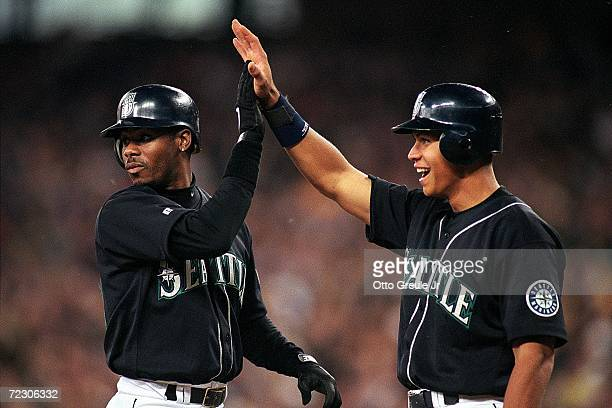 Ken Griffey Jr #24 and Alex Rodriguez of the Seattle Mariners hifiveing each other during the game against the San Diego Padres at Safeco Field in...