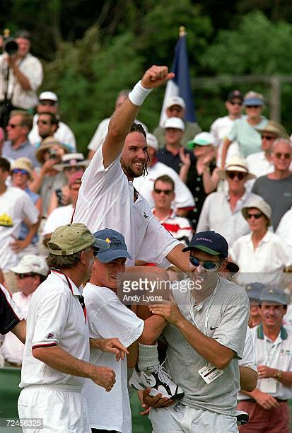 Patrick Rafter of Australia is being carried off by his teammates and celebrating his win after defeating Todd Martin of the USA 46 57 63 62 64...