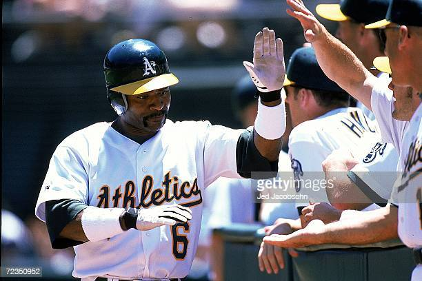 Tony Phillips of the Oakland Athletics high fives teammates during the game against the Texas Rangers at the Network Coliseum in Oakland California...