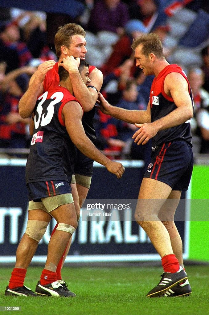 Jeff Farmer #33, David Schwarz #5 and David Neitz #9 for Melbourne celebrate a goal in the match between the Melbourne Demons and the Fremantle Dockers, during round 20 of the AFL season played at Colonial Stadium in Melbourne, Australia. Melbourne 25.10 (160) defeated Fremantle 11.11 (77). Mandatory Credit: Hamish Blair/ALLSPORT