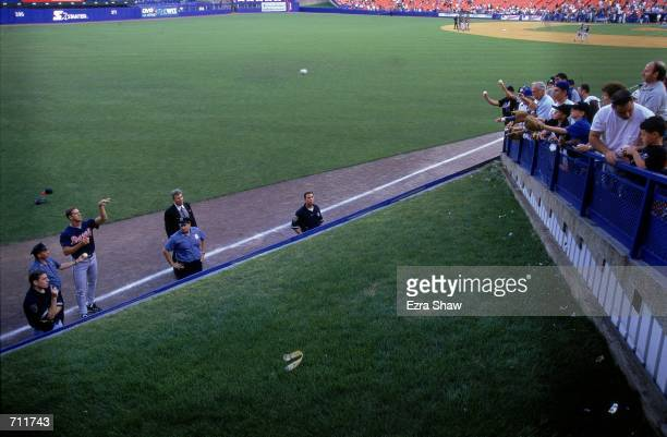 John Rocker of the Atlanta Braves tosses autograph baseballs to the fans during the game against the New York Mets at Shea Stadium in Flushing New...