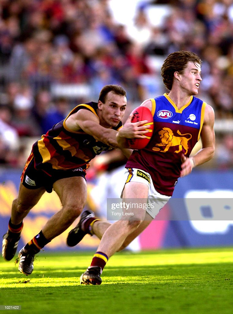 Luke Power # 6 for Brisbane evades a tackle from Tyson Edwards #9 for Adelaide in the match between the Adelaide Crows and the Brisbane Lions in round 20 of the AFL played at Football Park in Adelaide, Australia. Brisbane 17.13 (115) defeated Adelaide 11.12 (78) Digital Image. Mandatory Credit: Tony Lewis/ALLSPORT
