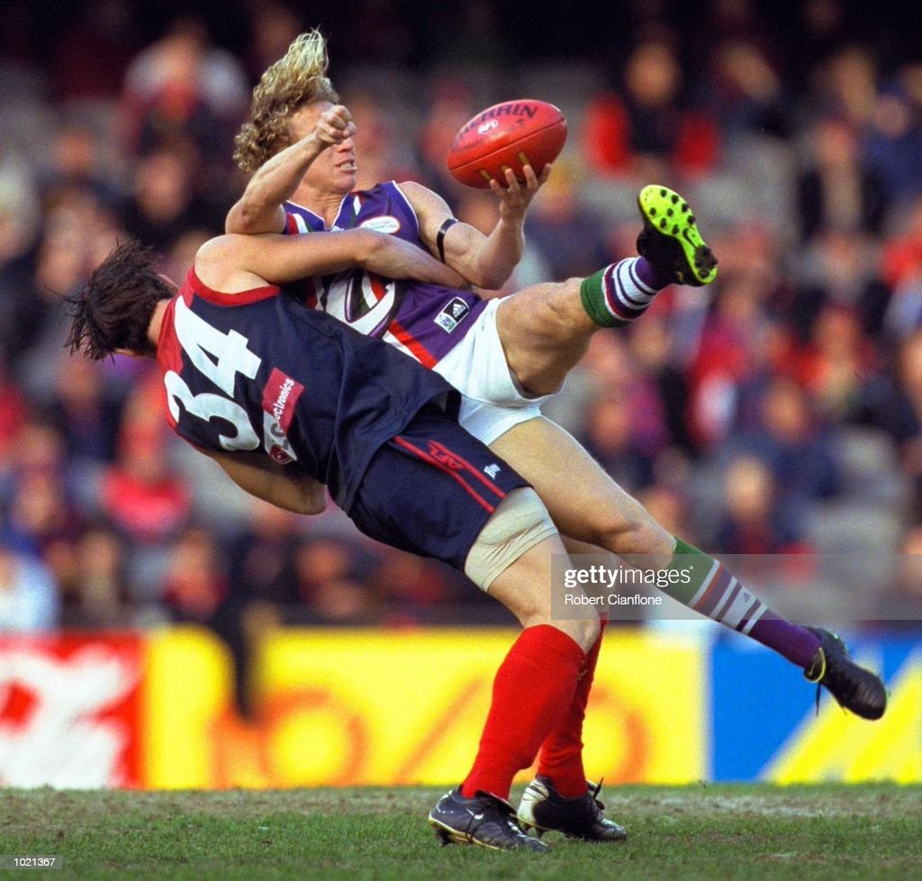 Shaun McManus #8 for Fremantle is tackled by Jeff White #34 for Melbourne in the match between the Melbourne Demons and the Fremantle Dockers, during round 20 of the AFL season played at Colonial Stadium in Melbourne, Australia. Melbourne25.10 (160) defeated Fremantle 11.11 (77). Mandatory Credit: Robert Cianflone/ALLSPORT