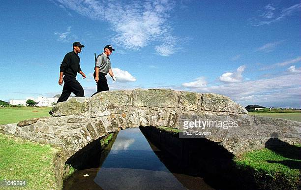 Tiger Woods and Mark O''Meara of the USA cross the Swilken Bridge on the 18th fairway during the second practice round at the British Open golf at St...