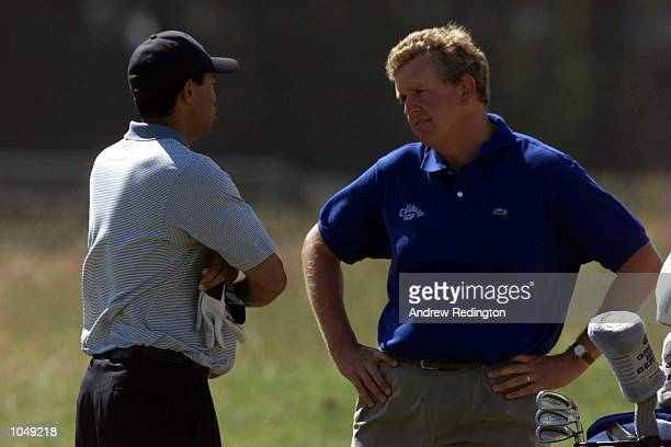 Tiger Woods of the United States shares a joke with Colin Montgomerie of Scotland during practice for the Open Championship at St Andrews Scotland...