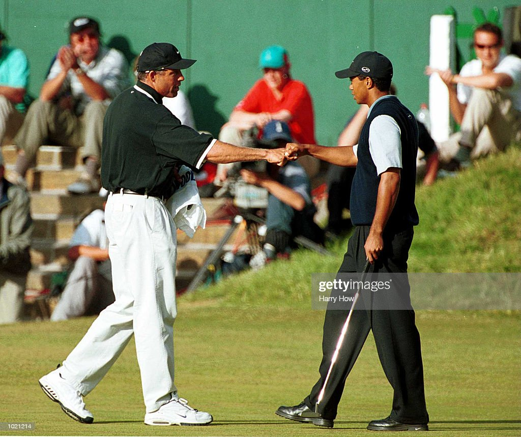 Tiger Woods of the USA celebrates with his caddie after holing a birdie putt on the 18th green during the third round of the British Open Golf Championships at the Old Course, St Andrews, Scotland. Mandatory Credit: Harry How/ALLSPORT