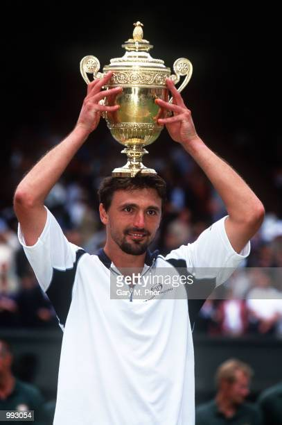 Goran Ivanisevic of Croatia poses with the trophy after winning against Pat Rafter of Australia in the Men's Final's of The All England Lawn Tennis...