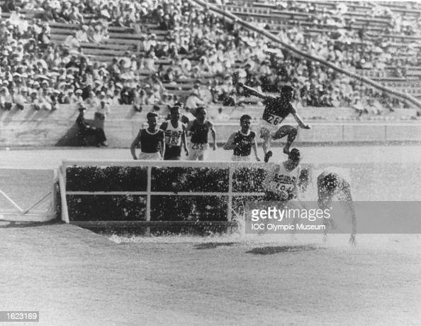 Competitors in action over the water jump during the 3000 metres Steeplechase event at the 1932 Olympic Games in the Coliseum Stadium Los Angeles USA...